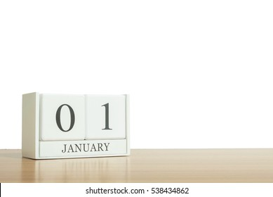 Closeup surface white wooden calendar with black 1 january word on blurred brown wood desk isolated on white background with copy space , selective focus at the calendar