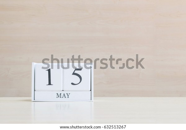 Closeup surface white wooden calendar with black 15 may word on blurred brown wood desk and wood wall textured background with copy space , selective focus at the calendar