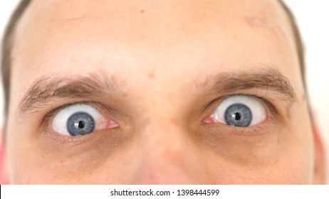 Close-up of a surprised emotional man with blue eyes looking into the camera.