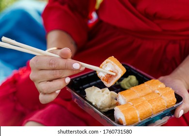 Close-up sushi set. Attractive girl in red dress holds sushi with chopsticks in hands. Courier delivered sushi set for pretty woman. Black box with sushi, wasabi, ginger.