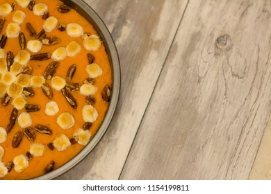 A closeup of a sweet potato casserole with pecans and marshmallows in a decorative snowflake design on a wooden table