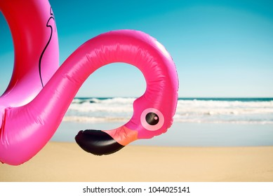 closeup of a swim ring in the shape of a pink flamingo on the beach, with the ocean and the blue sky in the background