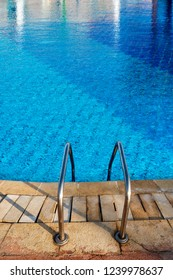 Close-up of a swimming pool with a blue water and a ladder in stainless steel