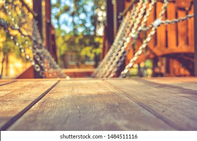 Close-up of swinging platform, hangs on chains in children's playground on sunny summer day as backdrop for outdoor activities and children's sports. Children's sports equipment on blurred background