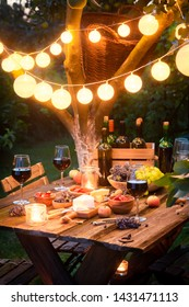 Closeup of table with appetizers and wine in illuminated garden
