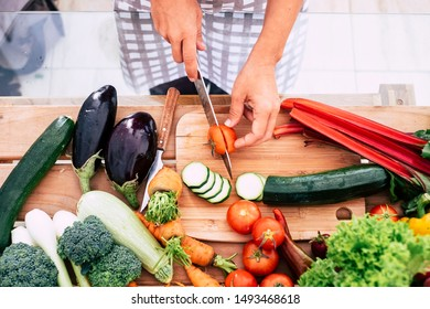 closeup of table full of vegetables like tomatoes, carrots and more - adult or senior cutting food inthe kitchen at home or restaurant - vegan and vegetarian lifestyle and diet