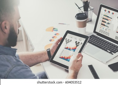 Close-up of a tablet computer with graphs, diagrams and charts on screen in hands of young bearded businessman sitting at table and working. On desk is laptop,cup of coffee,paper graphics, smartphone.