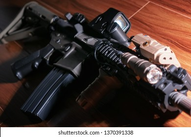 Close-up of tactical carbine on wooden floor, selective focus, hard lifgt