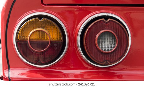 Closeup of the tail ights of a red classic car.