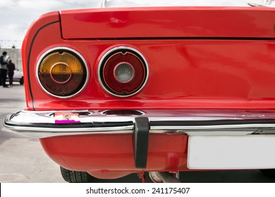 Closeup of the tail lights of a red classic car.