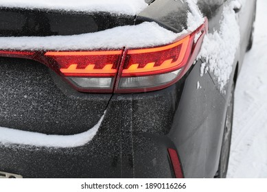 Close-up of a taillight on a car. Black car in white snow