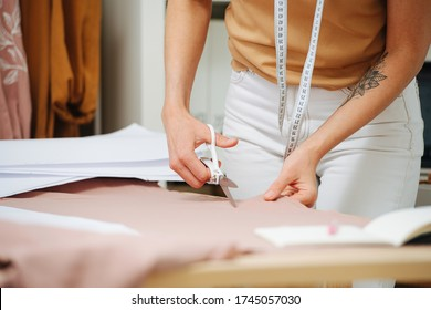 Close-up of the tailor hands with scissors, making a cut of the fabric