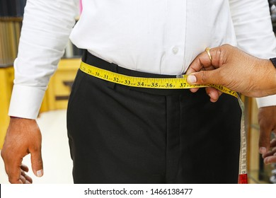 Closeup of tailor taking measurements of man waist with a measuring tape