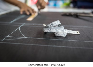 Closeup, Tailor working cutting fabric to a new coat with textile