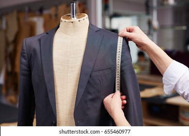 Closeup of tailors hands measuring jacket with tape fitting bespoke suit