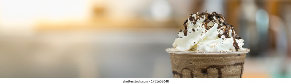 Closeup of takeaway plastic cup of coffee mocca frappe with whipped cream and chocolate sauce and chips with copy space. Using for cover page.