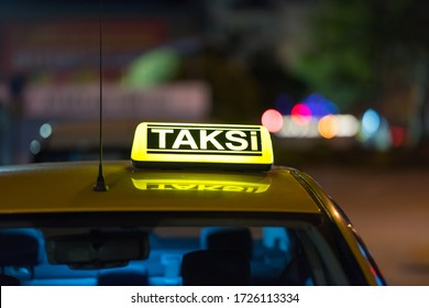 A closeup of a [taksi-taxi] sign on the car under the lights in the night with a blurry background