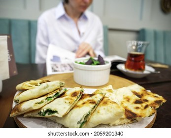 Close-up of tandir bread in Baku restaurant with silhouette of woman reading menu before in background