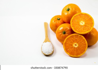 close-up tangerines slice on white background with salt on wood spoon, juicy tangerines on white space, fresh tangerines on white background