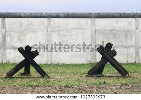Close-up of tank traps in front of concrete wall at inner german border