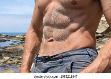 Closeup tanned abdominal and torso covered in sand of sexy muscular shirtless man on sunny day at beach