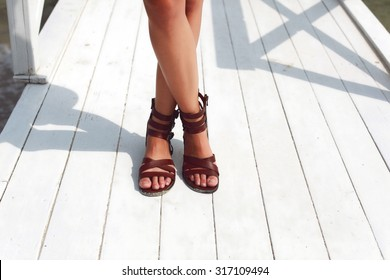 Closeup of tanned legs on wooden floor in summer