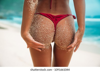 Close-up tanned parts of female body on the beach with white sand. Sexy model's ass in a red bikini. Women booties in a swimsuit on summer vacation.
