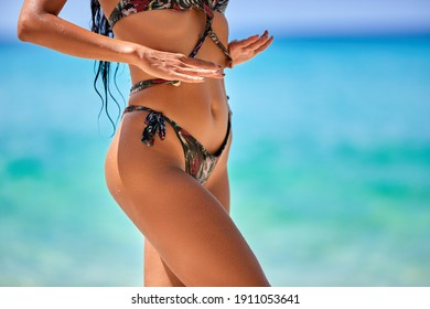 Close-up tanned parts of female body on the beach. Sexy girl with a beautiful slender figure against the sea in a colorful bikini on the blue water background