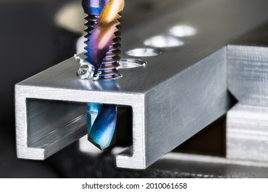 Closeup of tap and drill bit making a threaded hole in aluminum profile with metal shavings. Spiral twisted nano titanium coated product 2 in 1. Professional drilling and tapping tool. Chip machining.