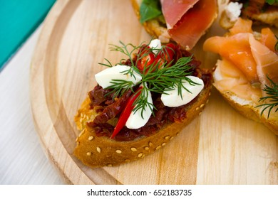 Closeup of tapas with tomato on white wooden table in summer restaurant