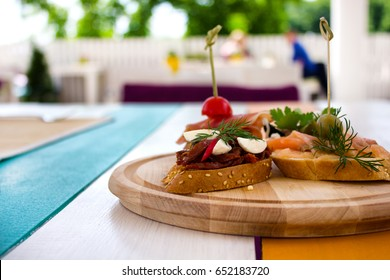 Closeup of tapas with tomato on  wooden table in summer restaurant