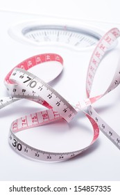 Close-up of a tape measure and Bathroom scale