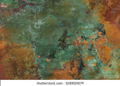Close-up of tarnished patina stained copper sheet metal that forms an abstract rich colorful pattern