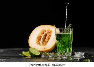 Close-up of a tarragon drink. A glass of green alcoholic cocktai. Cold herbal drink and melon on a black background. Copy space.