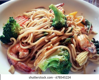 Close-up of tasty fried noodle with broccoli, shrimps, pepper and young corn