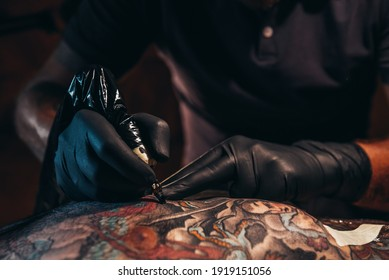 A closeup of a tattoo artist working on his latest piece of art work