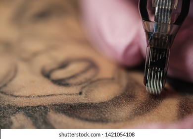 Close-up of a tattoo needle. The process of the tattoo master. Pink women's protective gloves. Tattoo sketch nun.
