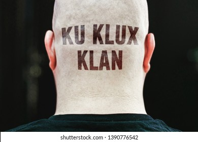 """A closeup of tattoo text """"KU KLUX KLAN"""" is imprinted on man's nape. A right-wing secret society in the US. - Shutterstock ID 1390776542"""
