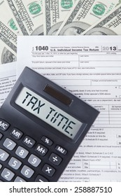 Closeup of tax time word with tax form, dollars cash, symbolizing the time to pay tax