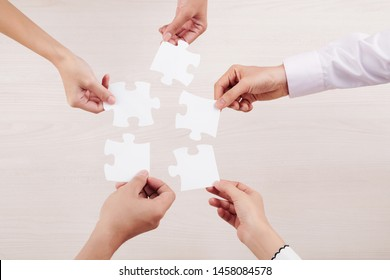 Close-up of team connecting their puzzles and demonstrating unity of friendship isolated on white background