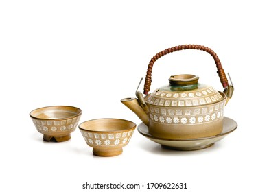 Closeup of teapot and cup set isolated on white background.