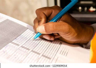 close-up of technician fill the maintenance form,Engineer write data in maintenance check list. writing a technical report about the manufacturing process
