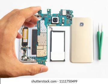 Close-up of technician holdinging smartphone logic boardon blurred smartphone component background