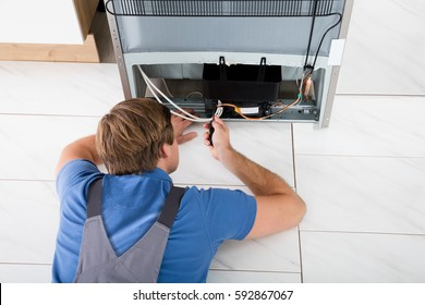 Close-up Of A Technician Repairing Refrigerator In Kitchen