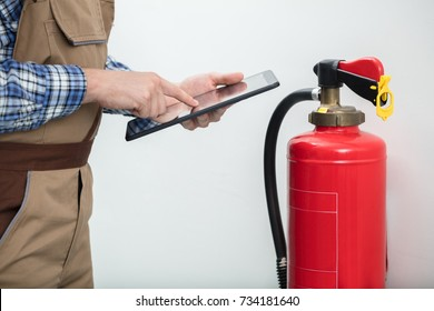 Close-up Of Technician Using Digital Tablet Checking Fire Extinguisher