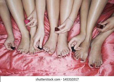 Closeup of teenage girls painting toenails on pink bedsheet