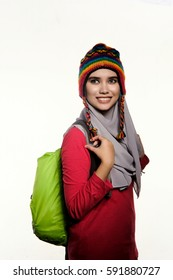 Close-up of a teenage muslim woman wearing a headgear, hijab and a backpack ready for hiking isolated on white background