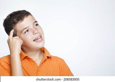 Closeup of a teenager boy thinking about something against gray background