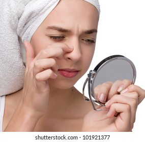 Close-up of teenager finding an acne on her nose wit towel on her head