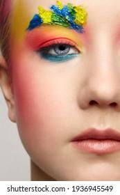 Nahaufnahme eines Teenagermädchens mit Halbbild-Porträt mit ungewöhnlicher Gesichtskunst-Make-up . Farbe auf Braun und Haar.